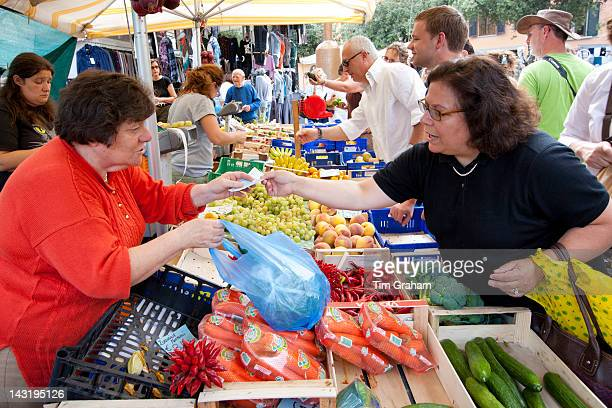 Woman selling fresh fruit at weekly street market in PanzanoinChianti Tuscany Italy