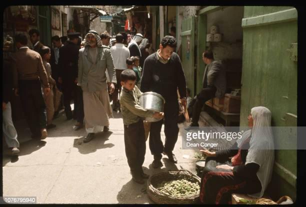 Woman Selling Fruit on Busy Sidewalk