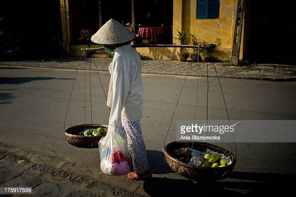 Woman selling fruits from the baskets on the street of Hoi An. As one of Unesco Heritage Sites a little and peaceful ancient town of Hoi An is...
