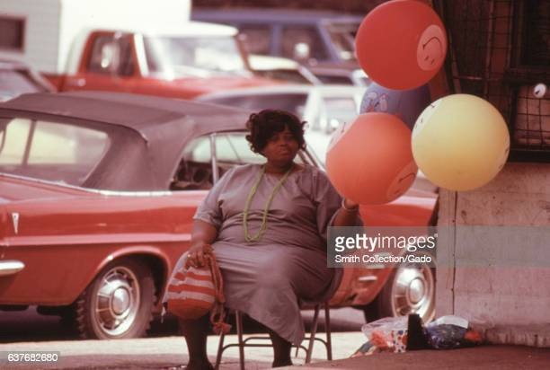 A woman selling gas holds 'Have A Happy Day' balloons on a side street corner at Sox Park Baseball Field in the South Side of Chicago Illinois 1973...