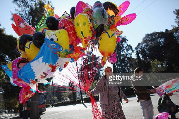 A woman selling helium balloons prepares to trade at a local festival on February 19 2012 in Athens Greece Following a meeting on Wednesday finance...