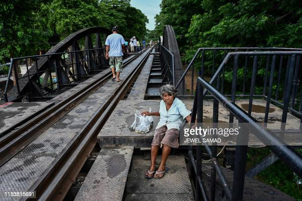 A woman selling live fish in plastic bags waits for customers on the railroad bridge over the Kwai Yai River in Kanchanaburi on July 5 2019