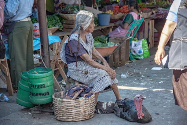 A woman selling live turkeys on the street