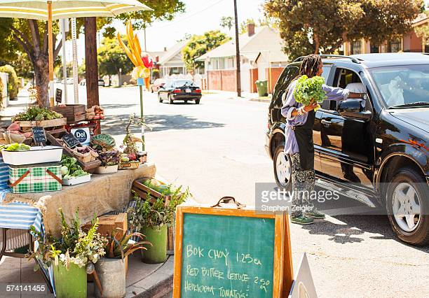 woman selling organic produce from a roadside stan - city of los angeles stock pictures, royalty-free photos & images