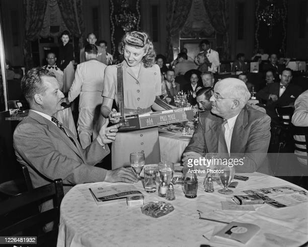 A woman selling Pall Mall cigarettes to two men in the Boulevard Room a supper club in the Stevens Hotel Chicago USA circa 1940