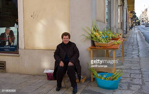 woman selling palm decorations for palm sunday, sicily - palm sunday stock pictures, royalty-free photos & images