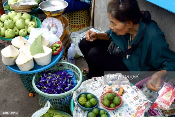 CONTENT] A woman selling purple edible flowers coconuts and fruit in the Mae Klong Market in Samut Songkhram Thailand taken in October 2013