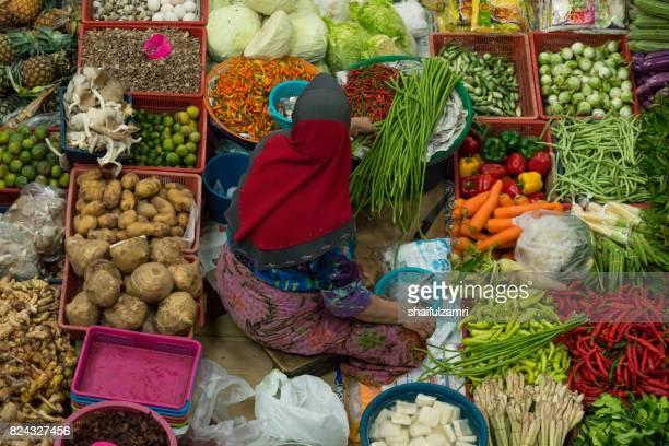 a woman selling various vegetables and local foods at kota bharu main market or famously known as pasar siti khadijah - shaifulzamri stock pictures, royalty-free photos & images