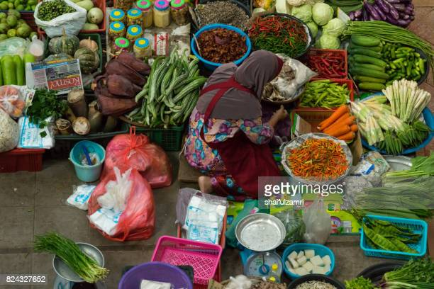 a woman selling various vegetables and local foods at kota bharu main market or famously known as pasar siti khadijah - shaifulzamri 個照片及圖片檔