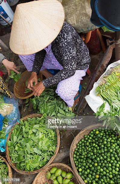 woman selling vegetables at market - chapeau chinois photos et images de collection