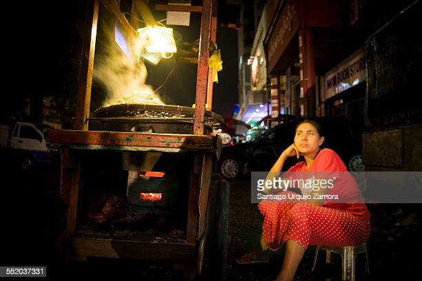 Woman selling warm food at night on her stall, Yangon, Yangon Region, Myanmar, Southeast Asia