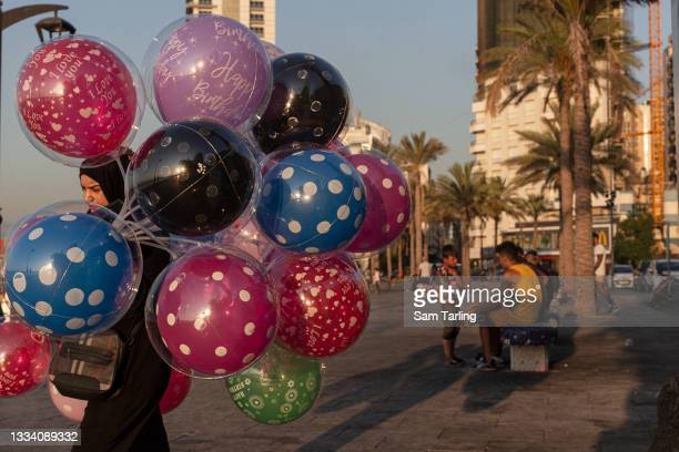 Woman sells balloons as children sell roses in Beirut, Lebanon, on August 13, 2021. Lebanon's economic crisis has resulted in a surge of children...