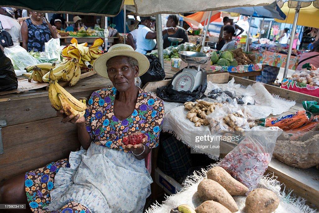 Woman sells bananas and fruits at market : Stock Photo