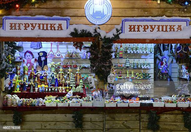 A woman sells Christmas gifts and Christmas Tree ornaments at a stall set up by GUM shopping mall near Red Square in Moscow Russia on December 10 2014