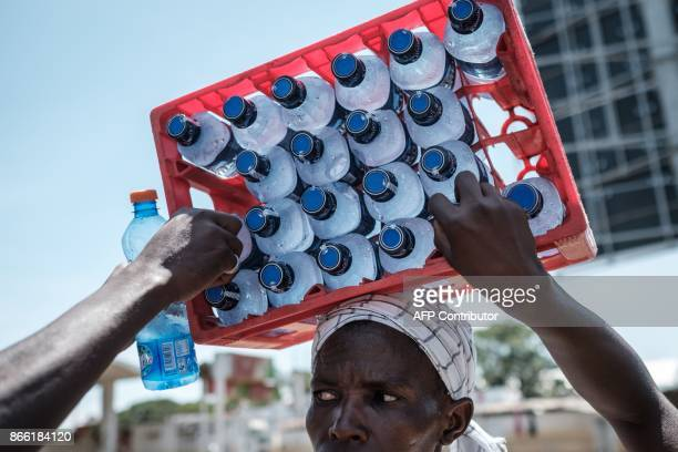 A woman sells cold water bottles that she carries on her head during a demonstration of supporters of the National Super Alliance presidential...