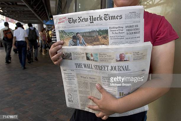 Woman sells copies of The New York Times and The Wall Street Journal newspapers outside the Port Authority Bus Terminal July 18, 2006 in New York...