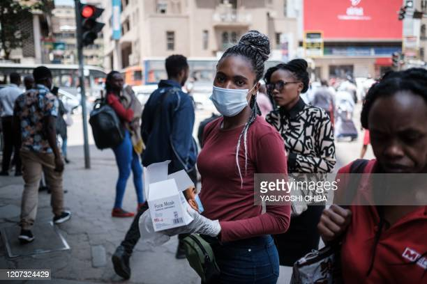 Woman sells face masks for 200 Kenyan shillings per piece, on a street, as a preventative measure, in downtown of Nairobi, Kenya, on March 16, 2020....