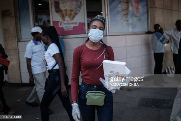 A woman sells face masks for 200 Kenyan shillings per piece on a street as a preventative measure in downtown of Nairobi Kenya on March 16 2020 Kenya...