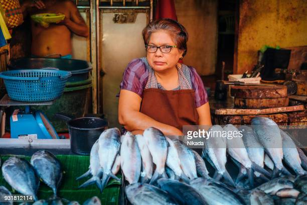 woman sells fish on street market in manila, philippines - philippines stock pictures, royalty-free photos & images