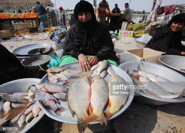A woman sells fish on the street as Iraqi soldiers and British soldiers from 1st Battalion The Yorkshire Regiment patrol the Al Qurnah market close...