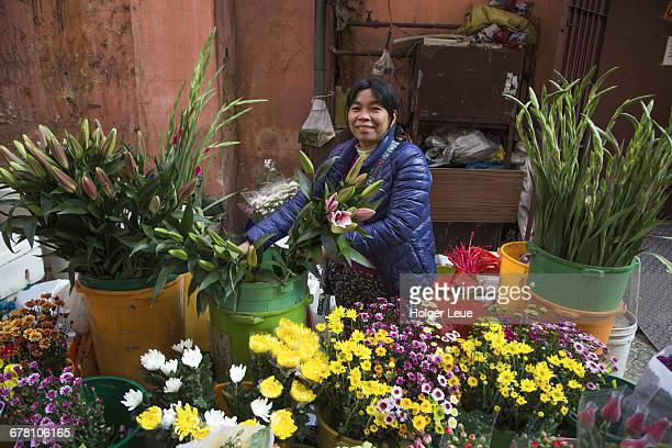 Woman sells flowers at street flower stand