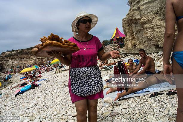 A woman sells goods as locals enjoy the beach on August 13 2015 in Sevastopol Crimea Russian President Vladimir Putin signed a bill in March 2014 to...