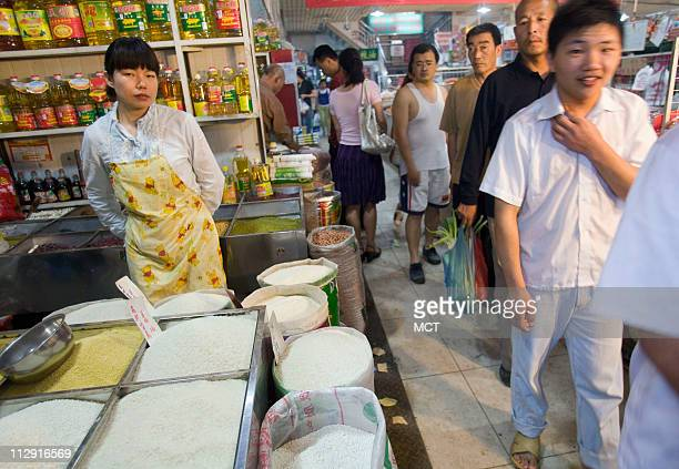 A woman sells grains and rice in a market in Beijing June 14 2008 A steady dietary transition is underway in China as the country grows more...