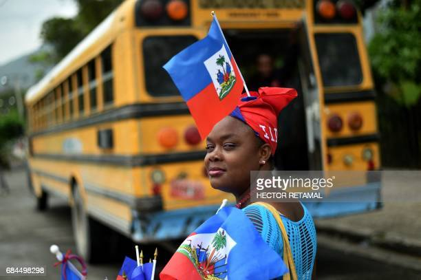 A woman sells Haitian national flags in Champ de Mars square in the center of the Haitian capital PortauPrince on May 18 2017 during Flag Day / AFP...