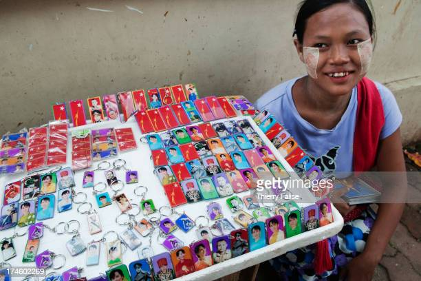 A woman sells key rings bearing portraits of Aung San Suu Kyi and her father Aung San founder of the country's independence are sold in a Yangon...