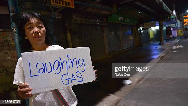 A woman sells laughing gas during curfew on Khao San Road street on May 27 2014 in Bangkok Thailand Khao San is a popular area with tourists and...