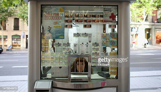 A woman sells lottery tickets from a booth on the affluent shopping street of Calle de Serrano on July 4 2012 in Madrid Spain Despite having the...