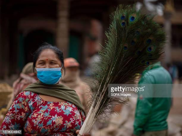 A woman sells peacock feathers while wearing a face mask during the festival at Hanuman Dhoka Sadak near Kathmandu Durbar Square Krishna Janmashtami...