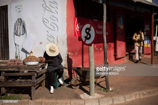 Woman sells peanuts outside the Oshoek border-post on the South African side of the border with Eswatini on July 2, 2021. - Calm returned to Eswatini...