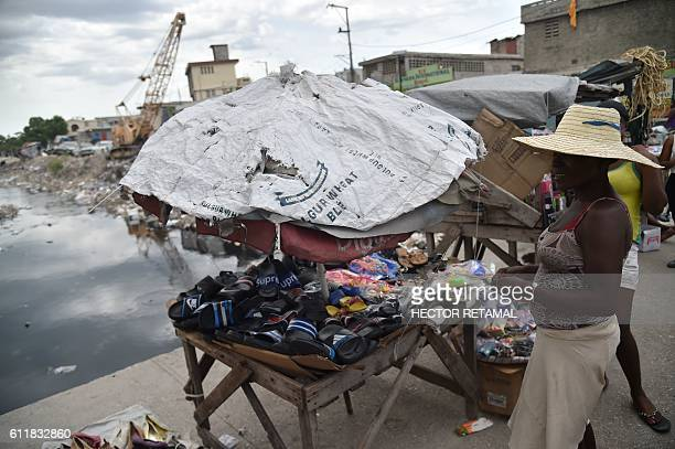 A woman sells sandals in a street near the canal of Portail Leogane in the Haitian capital PortauPrince on October 1 2016 As Hurricane Matthew...