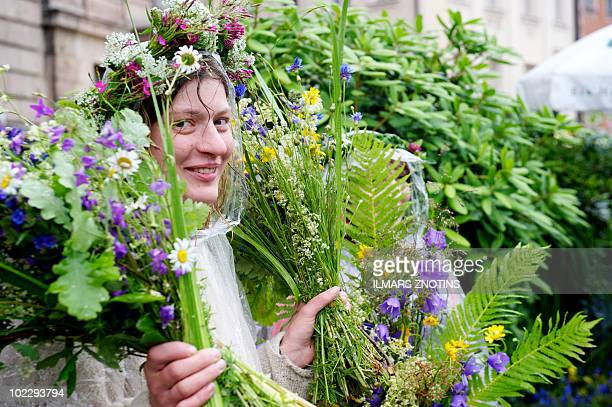 A woman sells traditional grass compositions and wreaths at a Grass Fair in Riga on June 22 2010 Latvians are getting ready for celebrating Latvia's...
