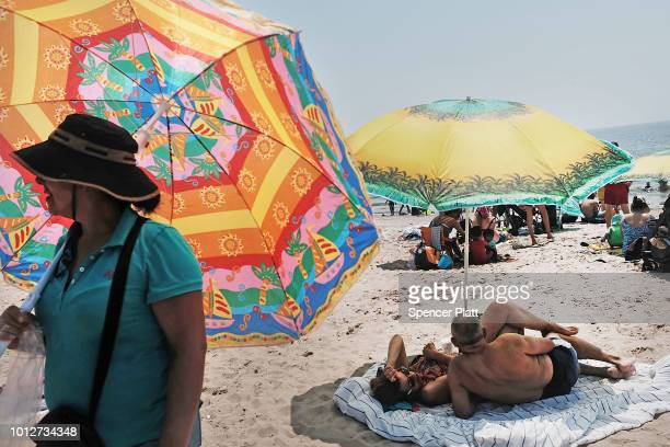 A woman sells umbrellas along the beach at Coney Island on a hot summer afternoon on August 7 2018 in the Brooklyn borough of New York City New York...
