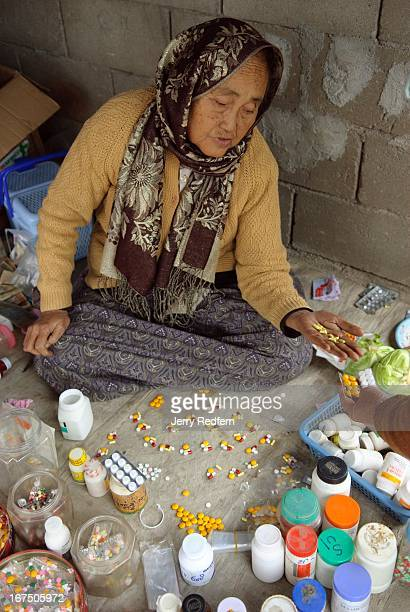 A woman sells various Chinese and Burmese medications at a stall at weekly market in rural Shan State Myanmar She didn't know what all of the pills...