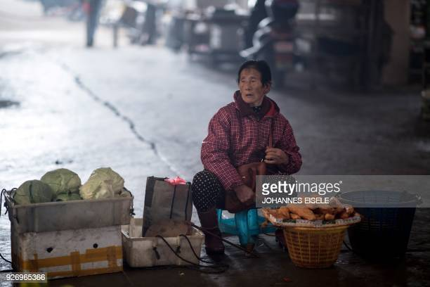 A woman sells vegetables at a market in Huangqi village near Lianjiang in Fujian province on March 4 2018 / AFP PHOTO / Johannes EISELE