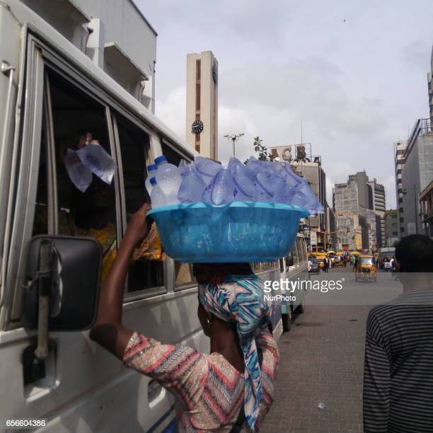 A woman sells water in traffic at Broad Street in Lagos Nigeria on Wednesday March 22 2017 Cost of getting quality water in Lagos is rising daily...