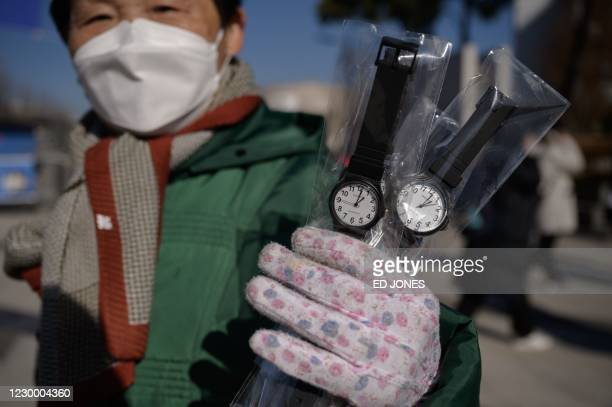 Woman sells wrist watches as high school students make their way to and from sitting 'Susi' college admissions exams, outside the gates of Yonsei...