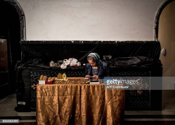 A woman sels candles in the Cathedral on the Blood in Yekaterinburg on August 19 2017 The Cathedral on the Blood is built on the spot where the last...