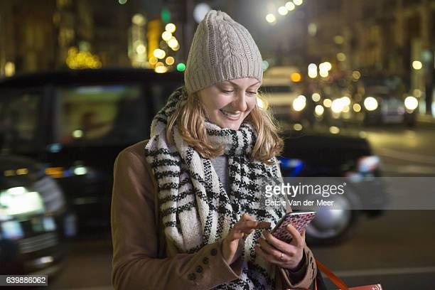 Woman send text on mobile phone, standing in urban street at night.