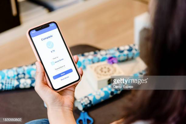 woman sending money to a friend through a mobile phone - exchanging stock pictures, royalty-free photos & images