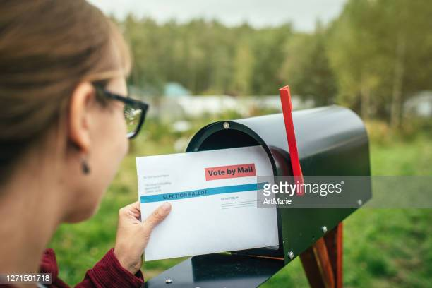 woman sending or receiving letter with voting ballot near a mailbox near her house - ballot slip stock pictures, royalty-free photos & images