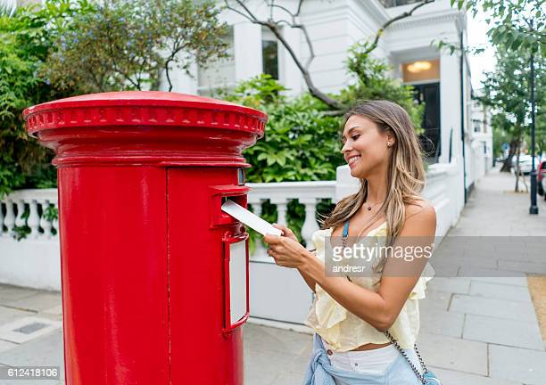 woman sending postcard through the mail - sending stock photos and pictures