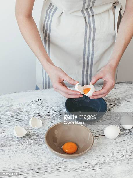 woman separating egg yolk and egg white - egg white stock pictures, royalty-free photos & images