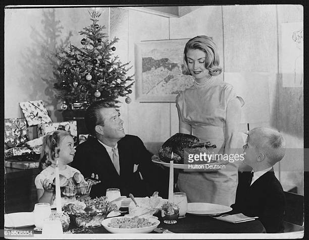 A woman serves a turkey to her family for dinner at Christmas time