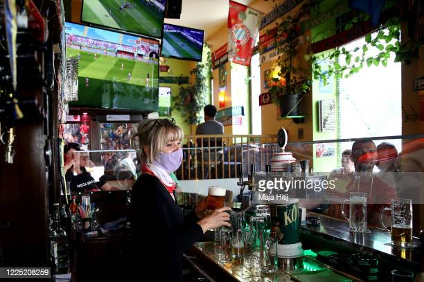 A woman serves beer to customers as fans watch the Bundesliga matches in a bar outside the Red Bull Arena during the Bundesliga match between RB...
