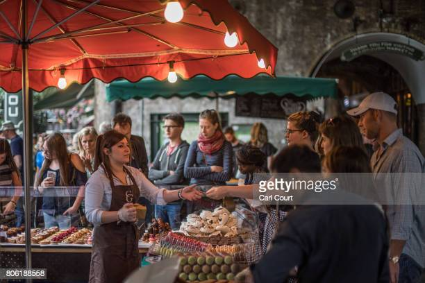 A woman serves customers at a stall in Borough Market on July 3 2017 in London England On 3 June 2017 Islamist terrorists attacked people with knives...