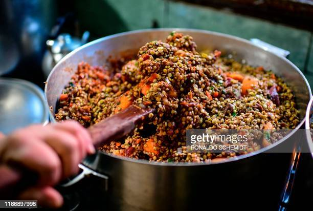 A woman serves food at a soup kitchen which feeds at least 200 people hit hard by the economic crisis at the Villa 2124 shantytown in Buenos Aires on...
